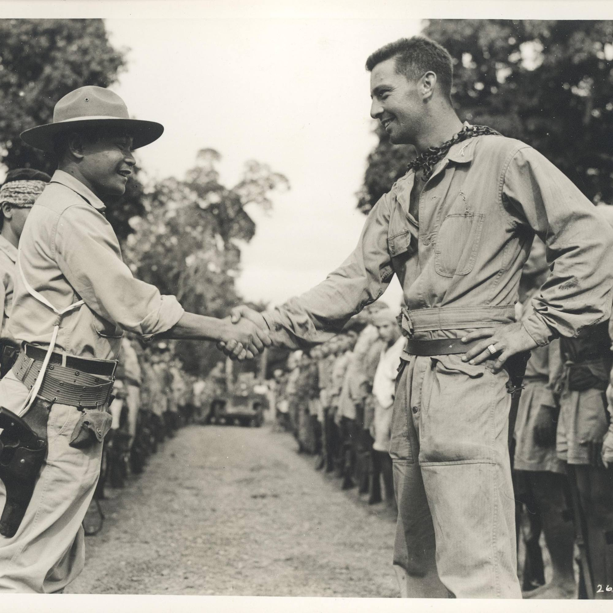 An American soldier and a Filipino soldier shake hands in the jungle while surrounded by more Filipino soldiers