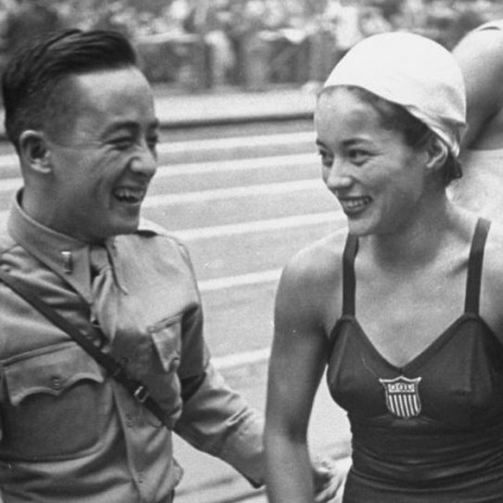 Black and white photo of a Filipino man in army uniform and a Filipina woman in a swimmers uniform, laughing